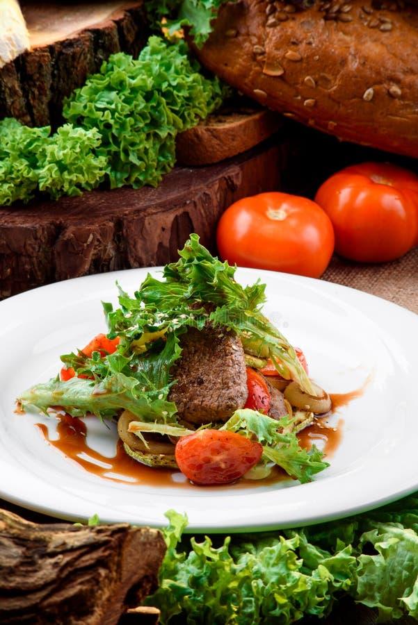 Carne grelhada com vegetais grelhados e alface fresca no molho do teriyaki na placa branca no fundo de madeira escuro fotos de stock royalty free