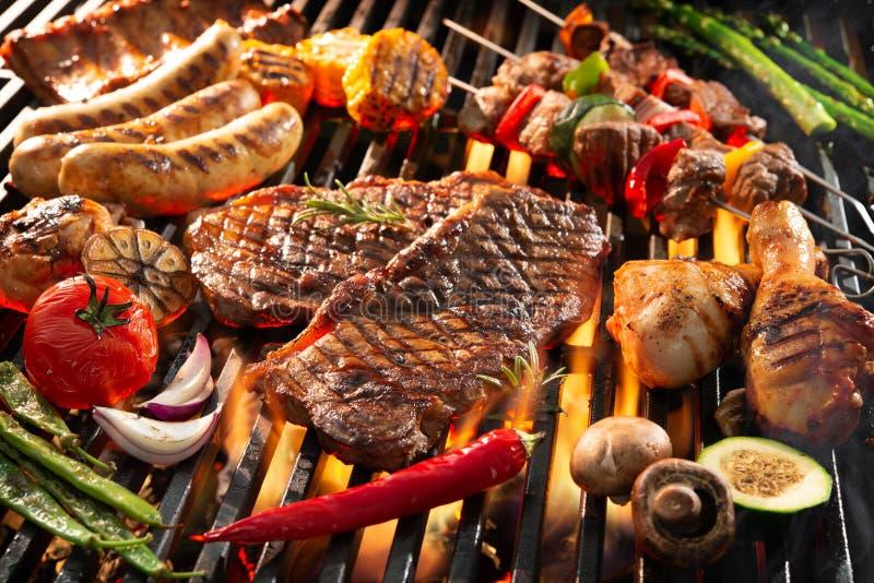 Carne grelhada deliciosa com os vegetais que chiam sobre os carvões no assado imagens de stock