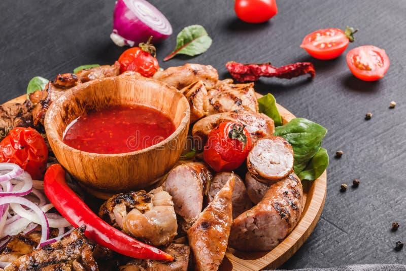 Carne grelhada deliciosa sortido e salsichas com tomates e molho do BBQ na placa de corte sobre o fundo de pedra preto Carne quen imagens de stock royalty free