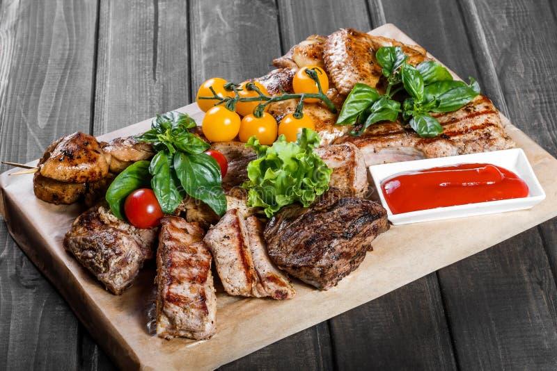 Carne grelhada deliciosa sortido e vegetais com salada fresca e molho do BBQ na placa de corte foto de stock