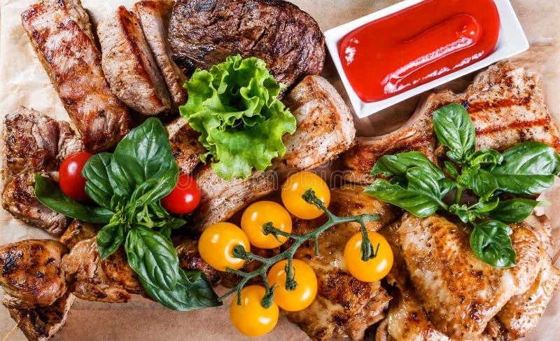 Carne grelhada deliciosa sortido e vegetais com salada fresca e molho do BBQ na placa de corte no fim de madeira do fundo acima foto de stock royalty free