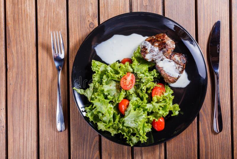 Carne grelhada do bife do beaf com salada e tomates do legume fresco na placa preta, fundo de madeira fotografia de stock