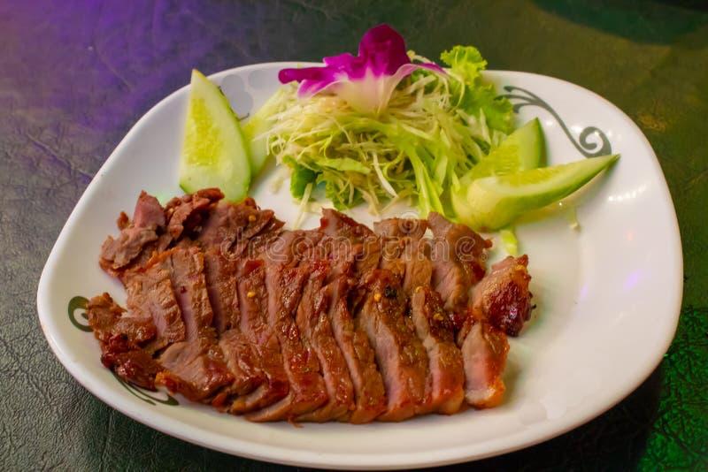 Carne grelhada em uma placa branca com o molho e os vegetais fotografia de stock