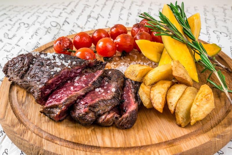Carne grelhada misturada, batatas, tomates com ervas imagem de stock