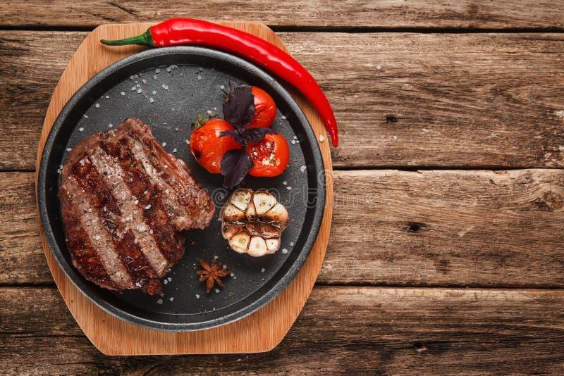 A carne grelhada na placa preta, plano coloca o espaço livre imagens de stock