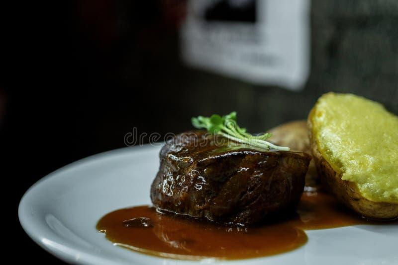 Carne grelhada suculenta do bife do close-up com molho de assado e as batatas enchidas em uma placa em um restaurante Almoço quen fotografia de stock