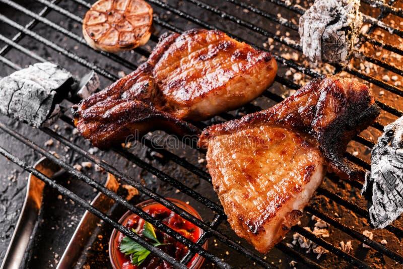 Carne grigliata con aglio sopra i carboni su un barbecue, fondo scuro della bistecca nella lombata con luce di fuoco Vista superi fotografie stock libere da diritti