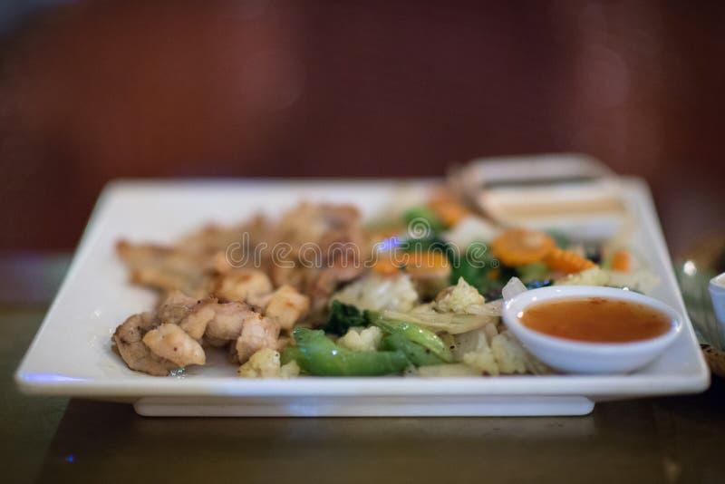 Carne grigliata dell'alligatore, raccordo del coccodrillo con le verdure su un piatto in un ristorante con barbecue di Siem Reap, fotografie stock