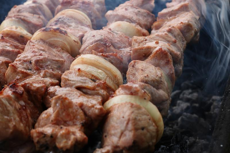 Carne grigliata sulla griglia sulla natura, sui carboni caldi, fumo fotografie stock