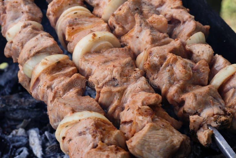 Carne grigliata sulla griglia sulla natura, sui carboni caldi, fumo immagine stock libera da diritti