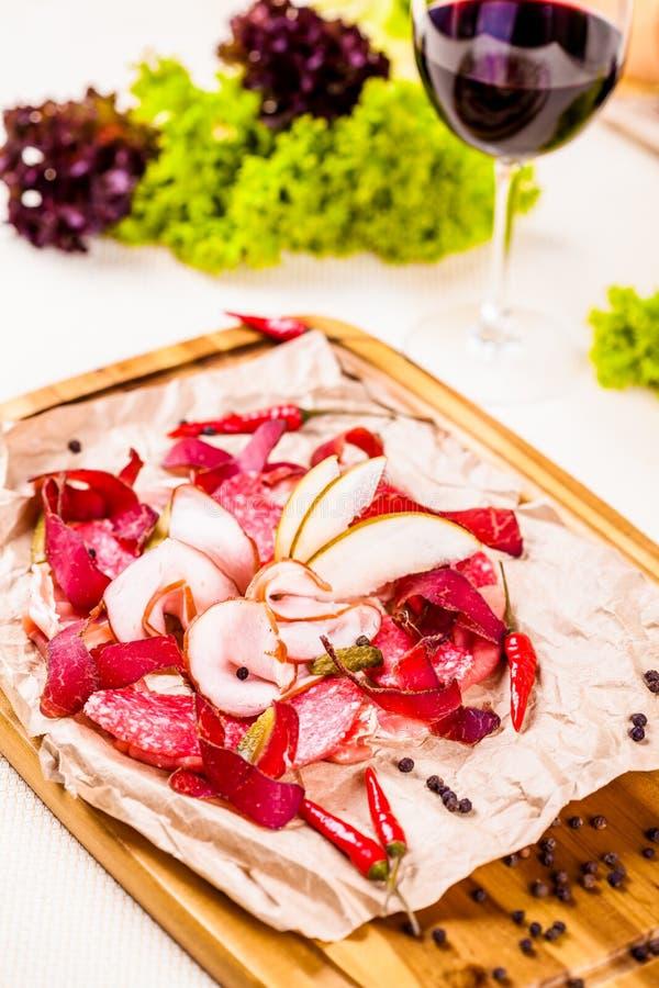 Carne italiana diferente com fatias e salmouras da pera na placa de madeira imagens de stock royalty free