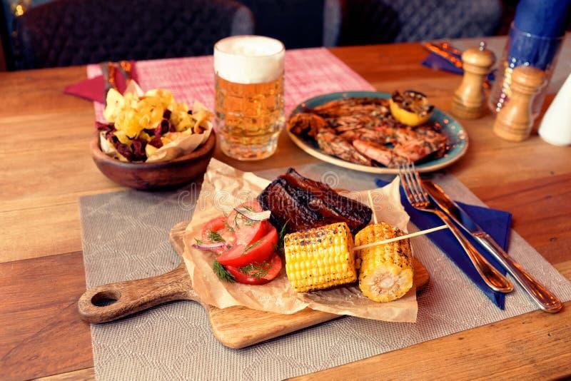 Carne, mais, patatine fritte grigliate e birra, tonificati fotografie stock