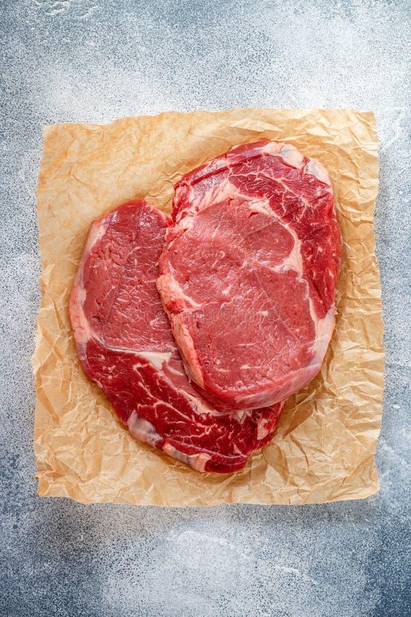 Carne marmorizzata organica fresca cruda Manzo, sale marino, pepe ed aglio sulla tavola Il nero Angus di Ribeye della bistecca de immagine stock libera da diritti