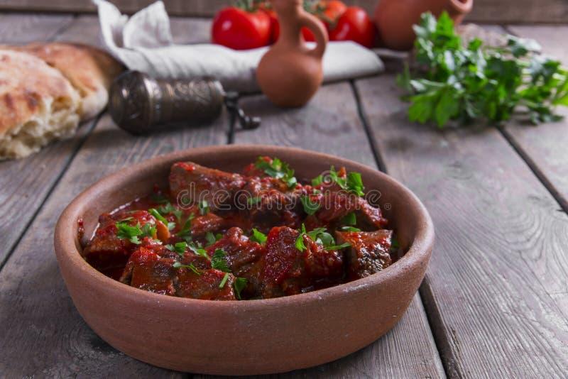 Carne no assado de carne do molho de tomate em uma bacia da argila imagens de stock royalty free