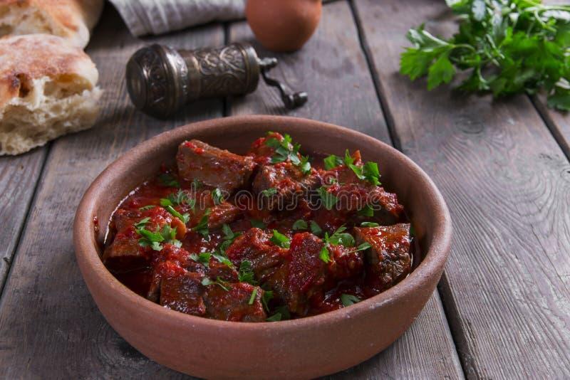 Carne no assado de carne do molho de tomate em uma bacia da argila fotos de stock