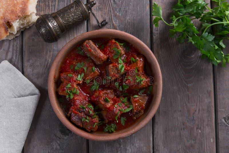 Carne no assado de carne do molho de tomate em uma bacia da argila fotografia de stock