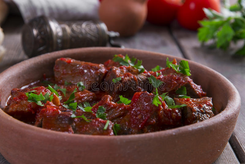 Carne no assado de carne do molho de tomate em uma bacia da argila imagem de stock royalty free