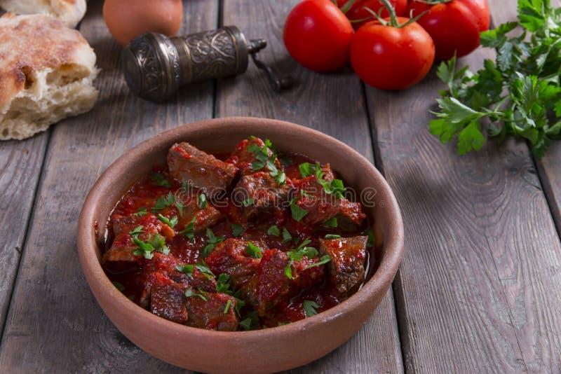 Carne no assado de carne do molho de tomate em uma bacia da argila imagem de stock