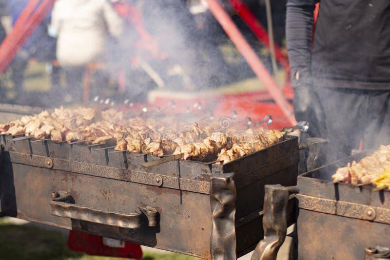 Carne nos espetos roasted na grade em uma nuvem de fumo foto de stock royalty free