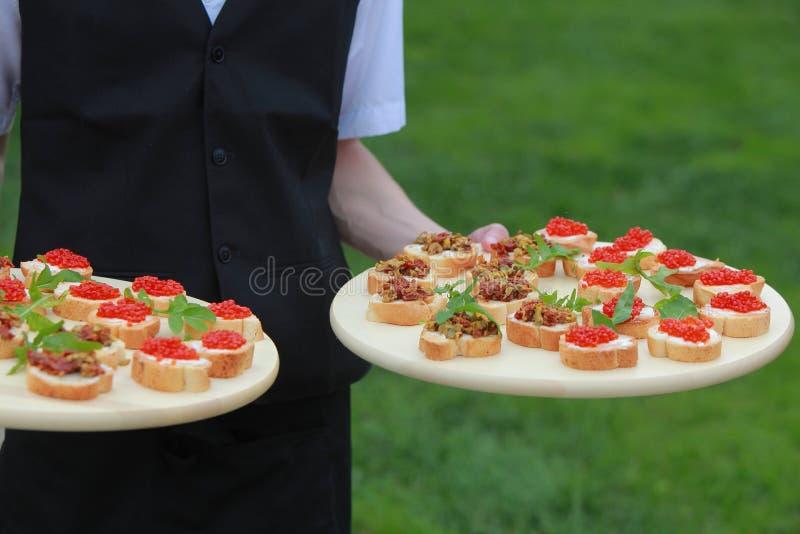 Carne, pesce, canapeson di verdure un vassoio nelle mani del cameriere all'aperto fotografia stock libera da diritti
