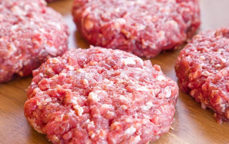 Carne picada cruda orgánica, empanadas redondas para hacer la hamburguesa hecha en casa en tabla de cortar de madera imagenes de archivo