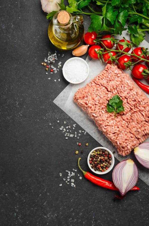 Carne picadita cruda en el papel con las verduras frescas y las especias en fondo negro fotos de archivo libres de regalías