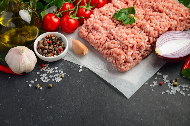 Carne picadita cruda en el papel con las verduras frescas y las especias en fondo negro imágenes de archivo libres de regalías