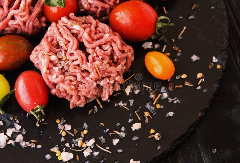 Carne picadita cruda, verduras con la sal y especias, foco selectivo imagen de archivo