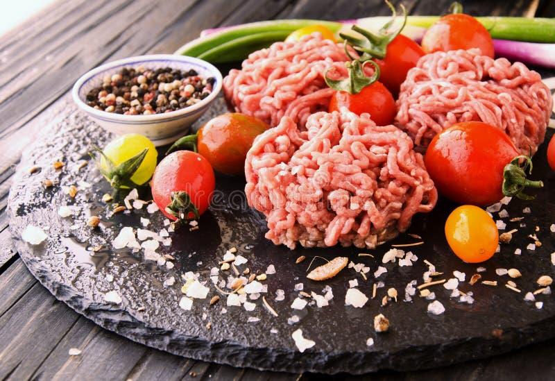 Carne picadita cruda, verduras con la sal y especias, foco selectivo imagen de archivo libre de regalías
