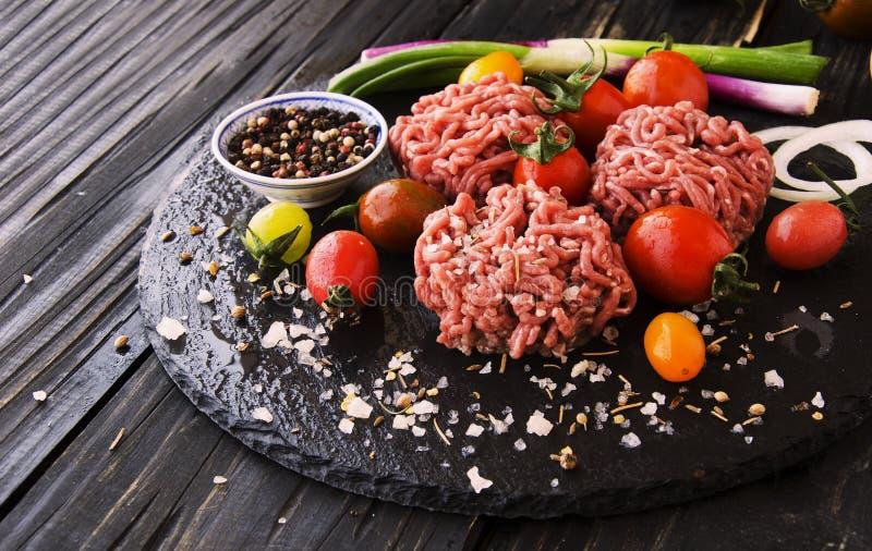 Carne picadita cruda, verduras con la sal y especias, foco selectivo fotos de archivo