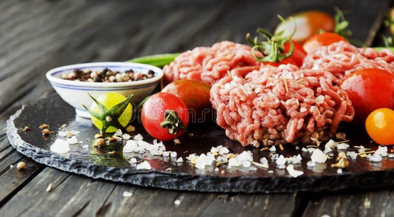 Carne picadita cruda, verduras con la sal y especias, foco selectivo imágenes de archivo libres de regalías