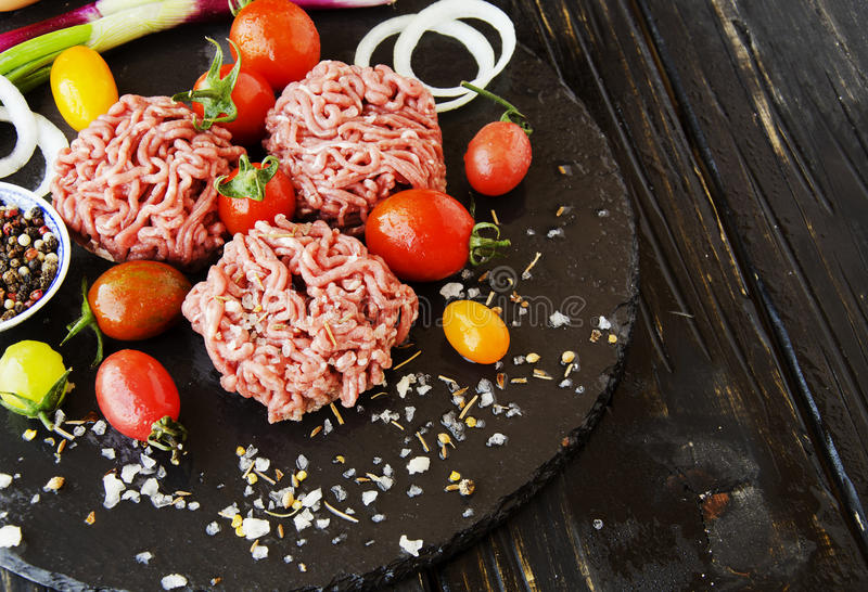 Carne picadita cruda, verduras con la sal y especias, foco selectivo fotos de archivo libres de regalías