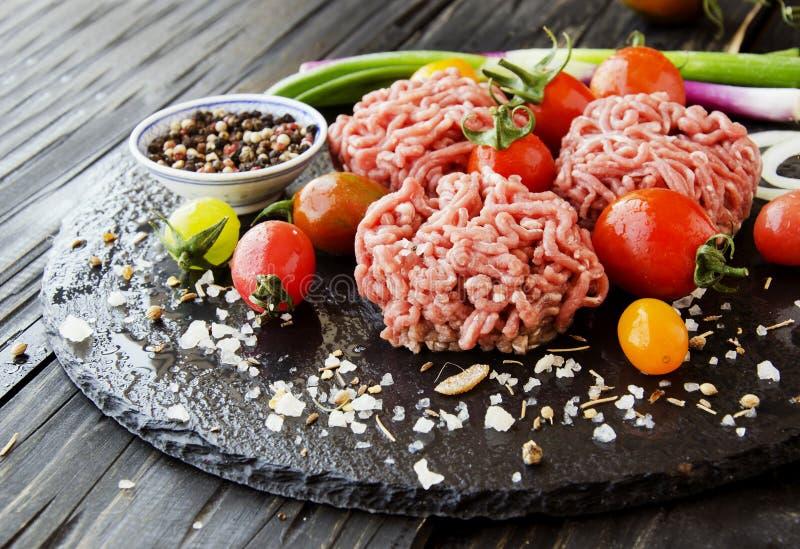 Carne picadita cruda, verduras con la sal y especias, foco selectivo fotografía de archivo libre de regalías