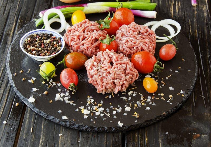 Carne picadita cruda, verduras con la sal y especias, foco selectivo foto de archivo