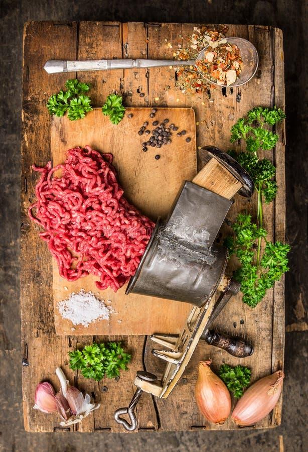 Carne picado de la máquina para picar carne del vintage en la tabla de madera vieja con las hierbas y las especias en cuchara imagenes de archivo
