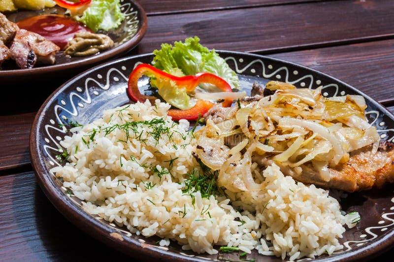 Carne, potatos, arroz, cebolla y ensalada de la verdura en restaurante en el escritorio de la madera imágenes de archivo libres de regalías