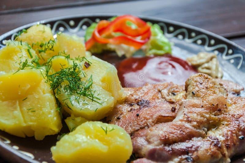 Carne, potatos, y ensalada de la verdura en restaurante en el escritorio de la madera fotos de archivo libres de regalías