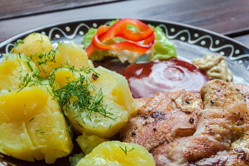Carne, potatos, y ensalada de la verdura en restaurante en el escritorio de la madera fotografía de archivo