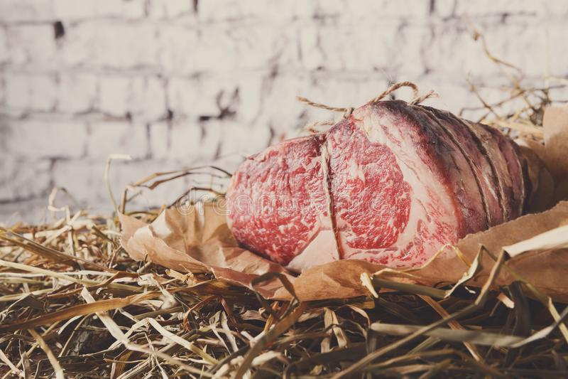 Carne preta principal envelhecida crua de angus no papper do ofício na palha foto de stock