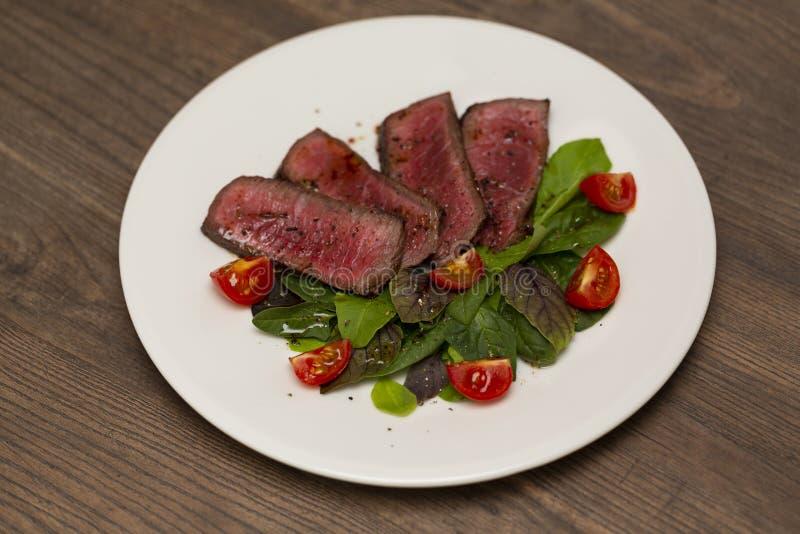 Carne rara suculenta do meio do bife com salada verde e tomates imagens de stock
