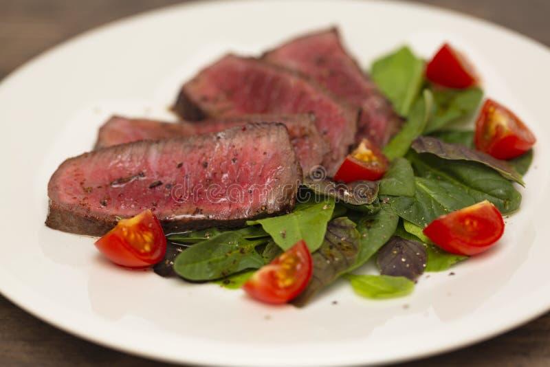 Carne rara suculenta do meio do bife com salada verde e tomates fotografia de stock royalty free