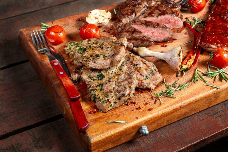 Carne, reforços e vegetais grelhados na tabela de madeira rústica imagem de stock