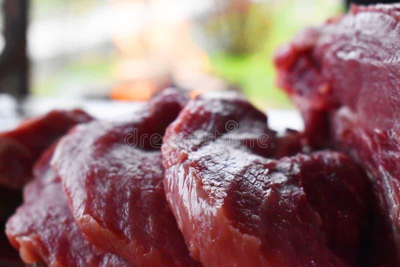 Carne roja cruda fresca en la tabla de madera lista para ser cocinado en la parrilla al aire libre del fuego Barbacoa en el jard? imagen de archivo