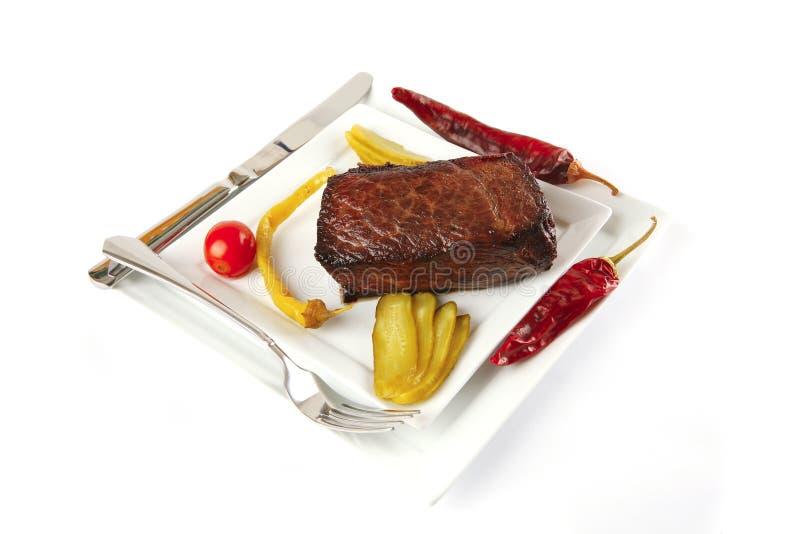 Carne roja y pimientas en blanco foto de archivo libre de regalías