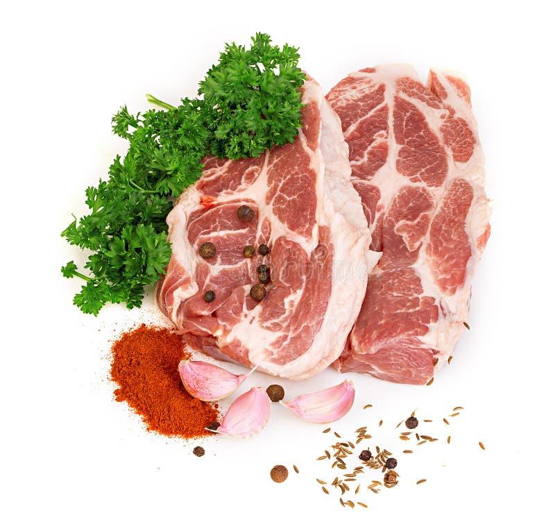Carne rossa fresca con le spezie ed il primo piano del prezzemolo su un fondo bianco immagini stock libere da diritti