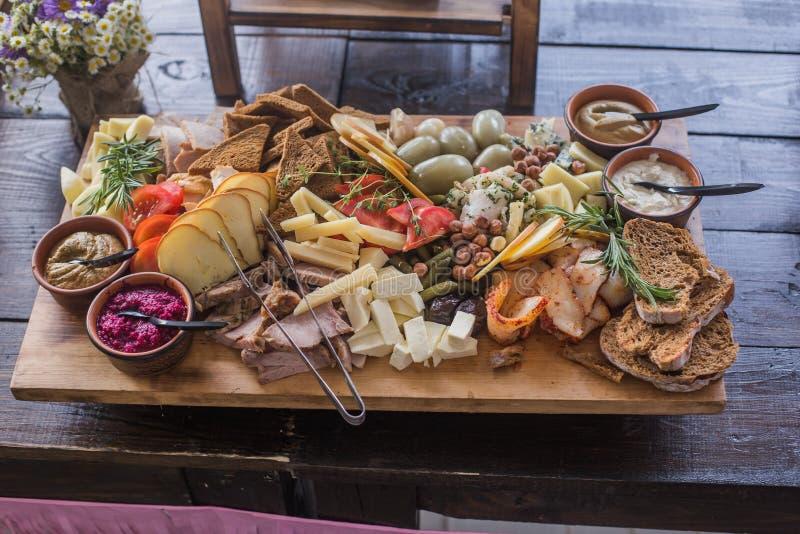 Carne, salchicha, jamón, frutas, verduras, aceitunas, conservadas en vinagre, pan y salsa curados queso clasificados para el acon imagen de archivo libre de regalías