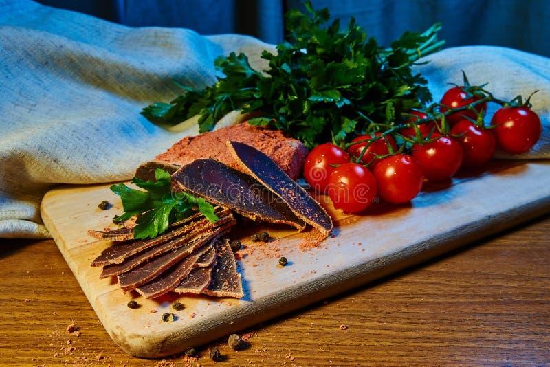 A carne secada, basturma encontra-se em uma placa de madeira com alcaparras e especiarias salsa fresca e tomates de cereja vermel imagens de stock