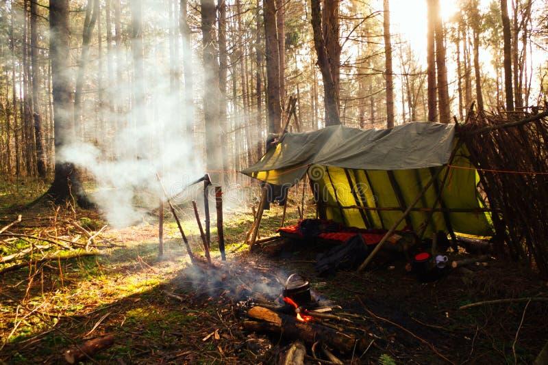 Carne sem gordura primitiva de Bushcraft ao abrigo com fogueira na região selvagem fotografia de stock royalty free