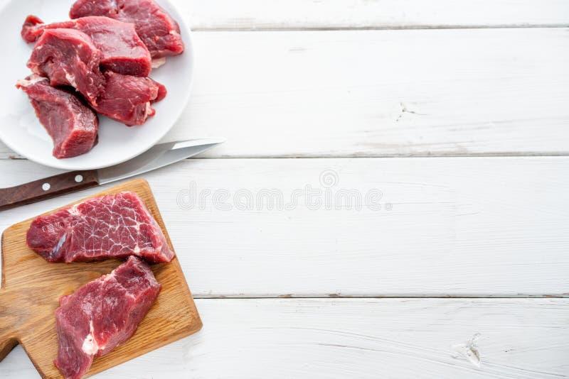 Carne sin procesar Filete de carne de vaca fresco crudo en una tabla de cortar y un cuchillo de talla de madera Fondo de madera b fotos de archivo libres de regalías