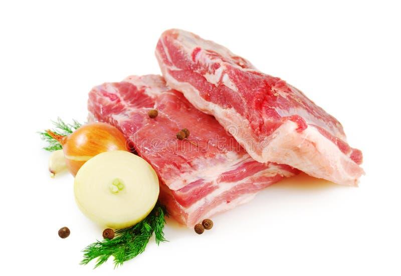 Carne sin procesar Vientre de cerdo, dos pedazos con eneldo, cebolla y tomate aislados en el fondo blanco foto de archivo libre de regalías